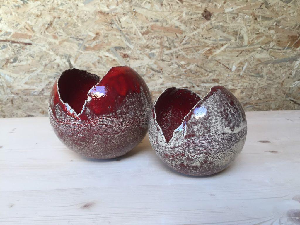 twee ronde vaasjes uit klei in mallen gemaakt, rood gevlamde glazuur