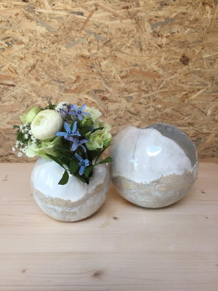 witte vaasjes of theelichtjes, vervaardigd in een malle met klei. Witte glazuur